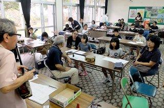 初心者体験教室で三線の基本について指導を受ける小学生ら=2日午後、県立石垣青少年の家