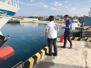 与那国島へ初めてのクルーズ船寄港に向けて、久部良漁港を視察する伊地知亮日本駐在マネージャー(右)=1日午前、同港(YVB提供)