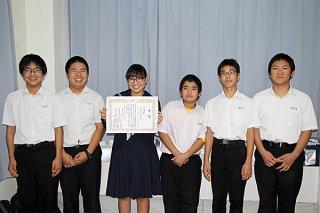 説明=第20回県中学校社会科新聞コンクールで、沖縄賞に輝いた崎枝中3年の野里実優さん(左から3人目)ら=4日午後、同校