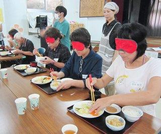 アイマスクをしての食事を体験する参加者ら=上原多目的施設