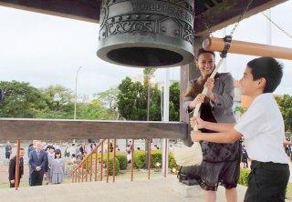 笑顔で平和の鐘を打ち鳴らす在日大使館関係者と児童=10日午前、世界平和の鐘鐘楼