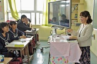 石垣第二中学校の職業人講話でアナウンサーの内原早紀子さん(右)の講話に耳を傾ける生徒ら=11日午後、同校