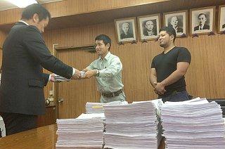 住民投票を求める有効署名1万4263筆を提出し、中山義隆市長に条例制定の請求書を手渡す金城龍太郎代表(中)ら=20日夕、庁議室