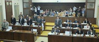 県民投票費を盛り込んだ補正予算案に起立して賛成する議員9人。少数で否決された=25日午後、本会議場