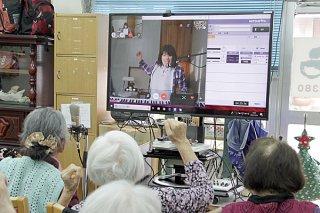 ビデオ通話を通じて運動の指示を出すモニターの音楽療法士=26日午後、あかゆらデイサービスセンター