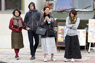 この冬一番の冷え込みに、マフラーなどで防寒する観光客ら=29日午後、730交差点