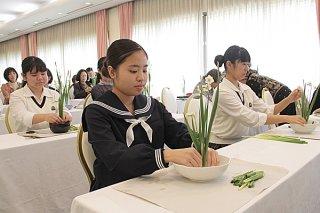 真剣な表情で水仙を生ける参加者たち=6日午前、アートホテル石垣島