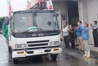 拍手を送り初出荷のトラックを見守るJA職員らと関係者=8日、与那国製糖工場内