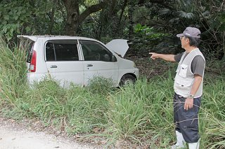 道路横の草むらに放置された軽自動車=2018年12月23日、黒島
