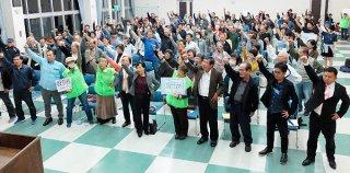 県民投票の実施を求め、「頑張ろう」と気勢を上げる集会参加者=14日夜、大浜公民館