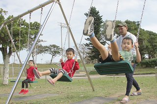 「久しぶりの公園」とブランコを楽しむ子どもたち=19日午後、石垣市中央運動公園こどもの広場