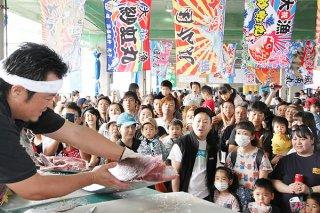 第17回お魚まつりのマグロの解体ショー。家族連れなどで人だかりができた=20日午前、八重山漁協セリ市場