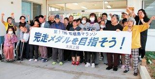 石垣島マラソンの出場者に「完走メダルを目指そう!」とエールを送る大浜工房の利用者たち=25日午前、同工房