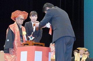 中山市長へ「あやかりの杯」を授ける浦崎致清さん(左)=5日午後、市民会館大ホール