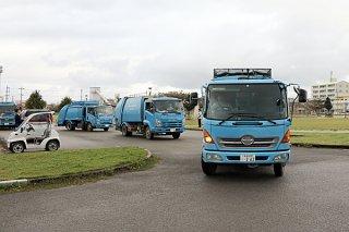 テープカットの後、広報業務を担い出発するゴミ収集車=8日午前、真栄里公園駐車場