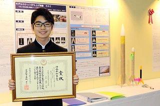 パネルに展示された研究ポスターと実験用ロケットの前で県知事賞を喜ぶ岡部壮良君=9日午前、「ANA ARENA 浦添」