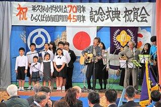 祝賀会で元気よく「はばたけ平久保っ子」を合唱する児童と園児、教職員ら=10日午後、同校体育館