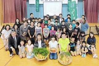 北部地区で収穫され、学校給食に納品されたニンジンに感謝する児童ら=15日午前、野底小学校