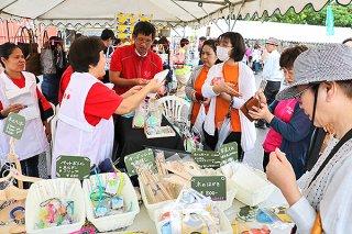 石垣島で初開催のナイスハートバザール。障がい者の手作り製品に人気が集まった=16日午前、マックスバリュやいま店駐車場