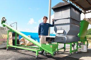 専門メーカーと協力して導入したもみ殻を燻炭に変える機械と林貴大さん=15日午前、山田精米所