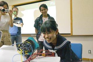 国内初公開されたクラスタ方式空気砲から射出されたパイナップルの香りを楽しむ八重山高校の生徒=19日午後、大浜信泉記念館