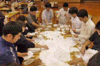 石垣市の開票作業を行う市職員。反対票は投票者数の7割を占めた=24日午後9時すぎ、石垣市総合体育館