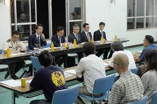 4地区住民の質問に答える沖縄防衛局の職員ら。春のカンムリワシ現況調査を3月に実施すると説明した=27日夜、川原公民館