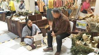 初めて名古屋市で開かれた与那国島フェアの伝統工芸ブースを訪れた来場者=1日午後、ららぽーと名古屋みなとアクルス(町商工会提供)