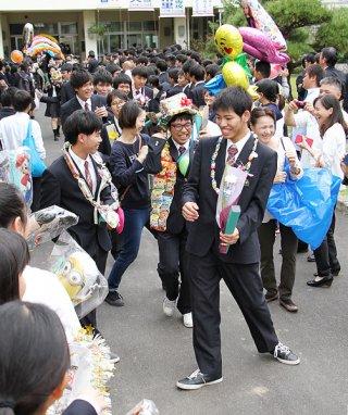 在校生や保護者らがつくる花道を笑顔で通り抜ける八重山商工高校の卒業生=1日午後、同校