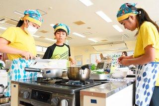 手際の良い調理で3品目を完成させる白保小学校の「さぶっ子6年生チーム」=2日午後、市健康福祉センター