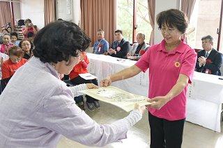 表彰式で石婦連の宮良和美会長から賞状を受け取る平得婦人会の大嶺洋子会長(右)=3日午後、市民会館中ホール2階会議室