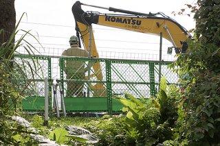 転圧作業を行うショベル。沖縄防衛局は5日、造成にかかる掘削工事を開始した=5日午後、旧ジュマールゴルフガーデン入り口付近