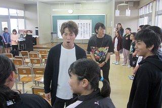 児童らの目を見て一緒に歌う劇団四季の高橋徹さん(中央)と塩地仁さん(後方)=8日、与那国小学校