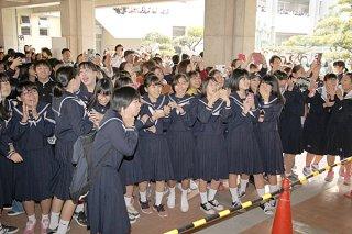 自分の番号を見つけて笑顔を浮かべる受験生たち=13日午前、八重山高校