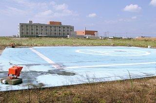 将来的に新石垣空港へ移設の可能性がある真栄里ヘリポート。奥の建物は八重山病院=2018年10月18日撮影