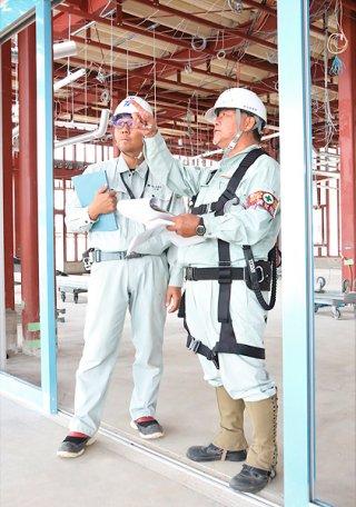 現場責任者(左)に安全対策について指導する安全指導員=18日午前、真栄里の八重山紫雲閣新築工事現場
