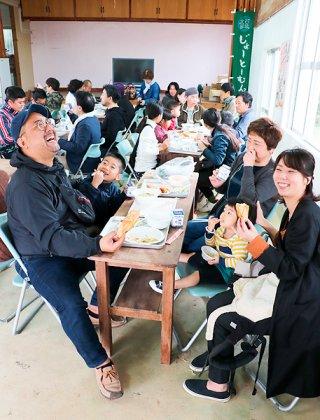 北部給食食堂の味を楽しみながらテーブルを囲む来場者ら=24日午前、栄公民館