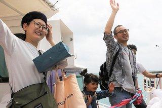 出港する船から手を振る石橋興介医師(右)ら家族=25日午前、竹富港