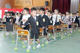 「ドキドキドン!一年生」を踊り、入学の喜びを表す新入生ら=9日午前、石垣小学校体育館