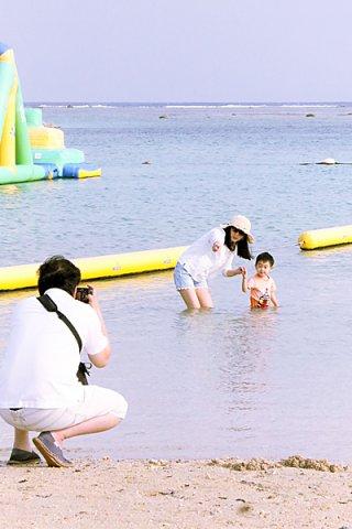 夏のような暑さに誘われ、ビーチで一足早い夏を味わう人たち=10日午後、マエサトビーチ