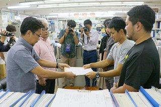 知念永一郎総務部長(左)から自治基本条例にかかる要請の回答書を受け取る金城龍太郎代表=16日午後、市役所
