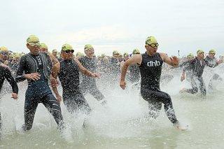 号砲の合図とともに波しぶきを上げて一斉に海の中に入っていく出場選手ら=21日午前、南ぬ浜町人工ビーチ