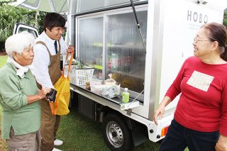 北部地区で移動販売や買い物代行などを行う移動冷蔵冷凍販売車「HOBO(ホーボー)」を利用する地域住民ら=7日午後、石垣市久宇良