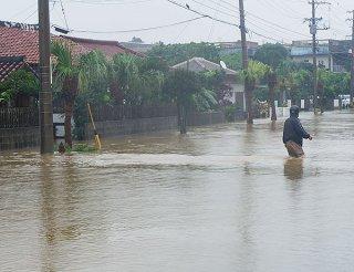 祖納を通る県道約200㍍にわたって冠水、川と化した=13日午前10時すぎ