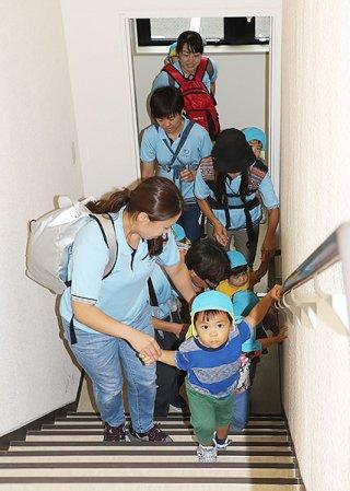 津波被害を想定して避難訓練する園児たち=15日午前、南の美ら花ホテルミヤヒラ美崎館