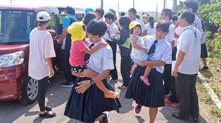 避難途中の保育園児らを抱き抱えて避難場へ駆け込む与那国中の生徒らと高台の避難場所へ向かう与小の児童ら=16日午前、町道