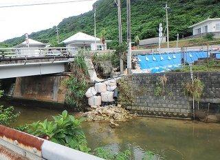 十山橋付近で崩落し土のうで応急措置された護岸。この影響で道路も片側通行止めになっている(八重山土木事務所提供)