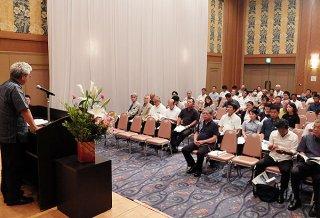 第56回通常総会で大松宏昭会長(左)のあいさつを聞く会員ら=23日夕、ANAインターコンチネンタル石垣リゾート