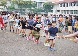 チャレンジデーの取り組みとして大縄跳びに挑戦する子どもたち。笑顔が広がった=29日午後、登野城小学校