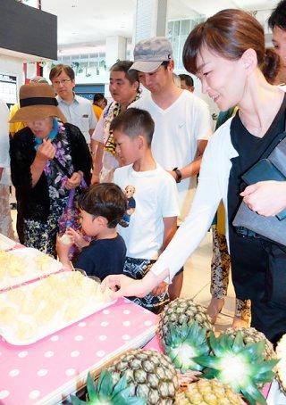 3種類のパインを試食する観光客ら。「おいしい」と満足していた=5月31日午後、南ぬ島石垣空港